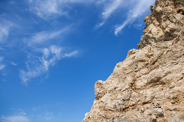 Rough rock with sharp edges and gentle clouds, like feathers on a blue sky