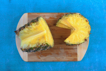 Large ripe pineapple on turquoise cement background in tropical theme.