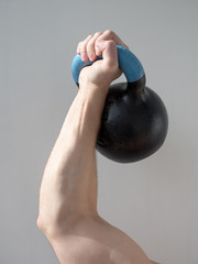 Man's hand holding dumbbell isolated on gray background. Close up, concept of healthy lifestyle.