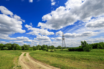 Fototapete - road and green field with trees and blue sky with clouds sunny day, beautiful rural landscape. Electricity tower standard overhead power line transmission tower