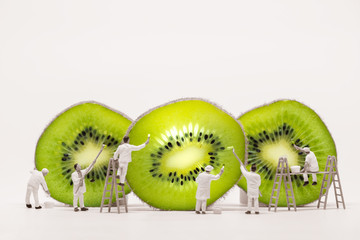 Miniature painters coloring Kiwi slices. Macro photo