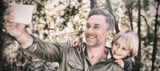 Smiling father and son taking selfie in forest
