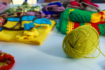 A tangle of woolen threads for knitting against the background of knitted clothes