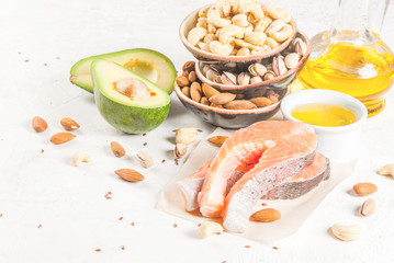 Healthy food. Products with healthy fats. Omega 3, omega 6. Ingredients and products: trout (salmon), flaxseed oil, avocado, almonds, cashews, pistachios. On a white stone table. Copy space