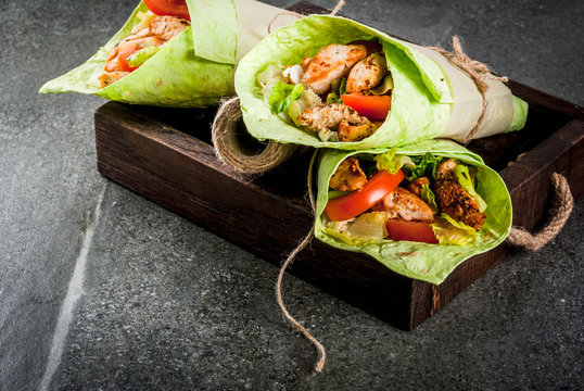 Mexican food. Healthy eating. Wrap sandwich: green lavash tortillas with spinach, fried chicken, fresh greens salad, tomatoes, yoghurt sauce. Wooden tray, dark stone table. Copy space