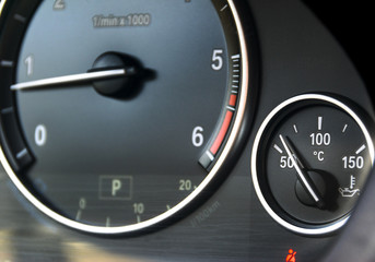 Coolant temperature gauge and tahometer on a car's dashboard. Car interior details. Close up view