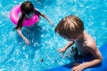 young girl and boy in pool looking at dive toy