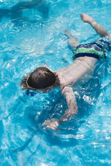 young boy with diving mask underwater in pool