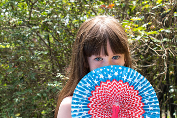 young girl hiding face behind fourth of july fan