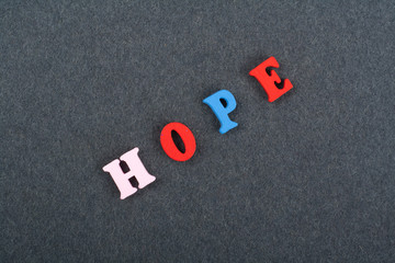 HOPE word on black board background composed from colorful abc alphabet block wooden letters, copy space for ad text. Learning english concept.