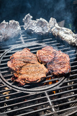 Two steaks on round grill with tinfoil sides over fire