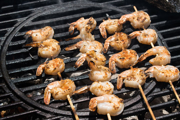 Shrimp kababs on round grill over coals