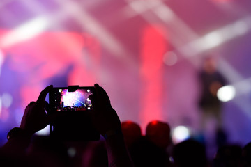 Man at a concert shooting video or photo.