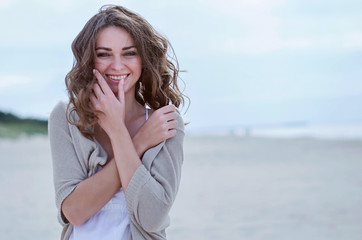Woman face Portrait on the beach. Happy beautiful curly-haired girl close-up, the wind fluttering hair. Spring portrait on the beach. Young pretty girl. Young smiling outdoors portrait. Close. ocean.