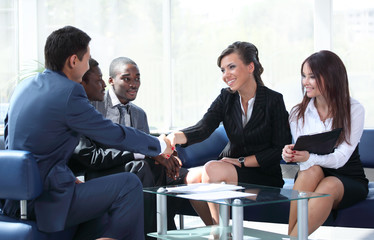 Confident business partners working in office and shaking hands