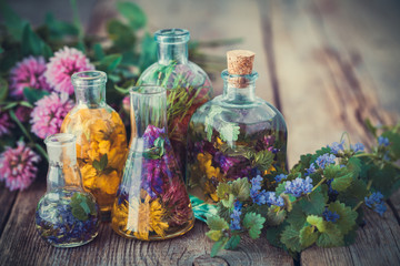 Bottles of tincture or infusion of healthy herbs, healing herbs on table. Herbal medicine.