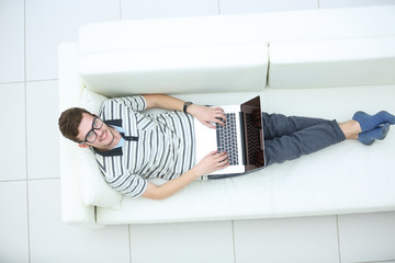 Top view of happy young man using his laptop in bright living ro