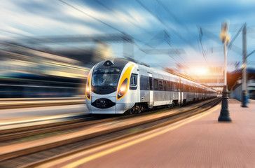 High speed train in motion at the railway station at sunset. Modern european intercity train on the railway platform with motion blur effect. Industrial scene with moving passenger train on railroad