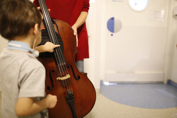Woman with cello visiting hospital