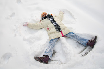 Young girl making a snow angel