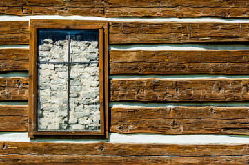Rustic timber wall with window blocked by rocks