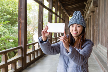 Woman taking photo with cellphone in japanese old house