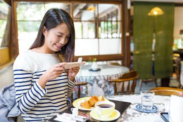 Woman taking photo on her breakfast