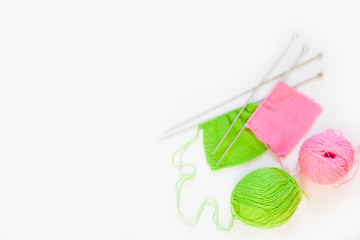 Knitted fabric of green and pink. Yarn for knitting green and pink. White background.
