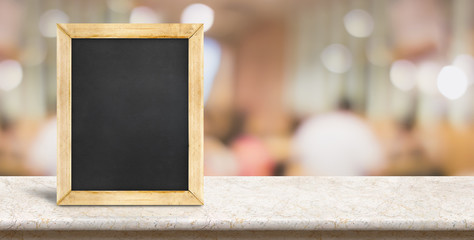 Blank blackboard on marble table in front of blur people dining at restaurant background,panoramic banner for display or montage of product or design,Food concept