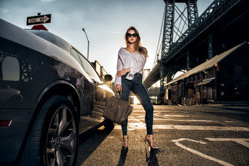 Beautiful fashion model woman posing with a car wearing casual street style outfit Wall mural
