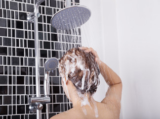 woman washing head and hair in the rain shower by shampoo, rear view