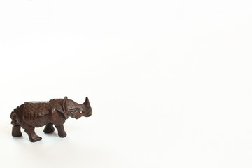 Hand carved wooden rhinoceros standing looking right isolated on white background
