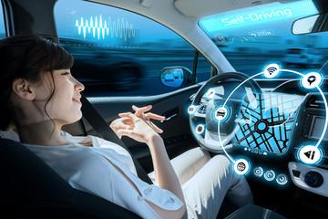 woman riding autonomous car. self driving vehicle. autopilot. automotive technology. Wall mural