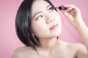 Long hair asian young beautiful woman applying mascara isolated over pink background. natural makeup, SPA therapy, skincare, cosmetology and plastic surgery concept.