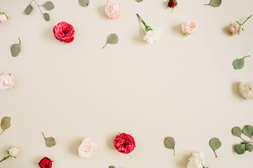 Flowers frame made of beige and red roses, eucalyptus leaf on pale pastel beige background. Flat lay, top view. Floral wreath frame background.