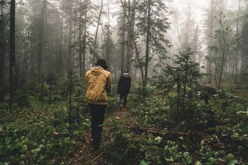 guys walking through a fog forest