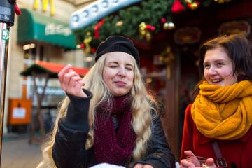 Freunde, Mann, Frau, Paar haben Spaß auf dem Weihnachtsmarkt, lachen, scherzen, trinken Glühwein mit Alkohol und freuen sich in Winterbekleidung