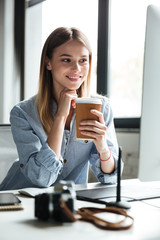 Smiling young woman work in office using computer drinking coffee.
