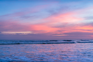 Blue Ocean Wave Crashing at Sunset. Long exposed photo of a sunset coast, Indonesia. Beautiful sunset on the Indian ocean. Orange beach pattern. Surfing Waves on the Tropical Beach. Panoramic Sunset