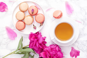 Tea time. Flat lay over light background with peonies, macaroons and cup of tea