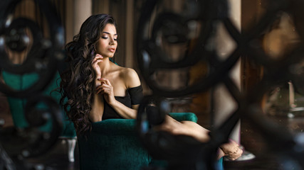 The image of a beautiful luxurious woman sitting on a vintage couch