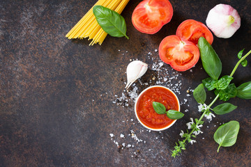 Culinary background for cooking pasta, tomato sauce, fresh herbs and spices. Copy space.