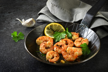 prawns shrimps with garlic, lemon, spices and italian parsley garnish in a black pan on a dark slate plate