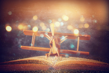 Toy plane and the open book on wooden table with glitter lights