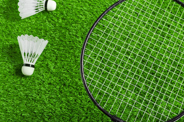 Shuttlecock and badminton racket on green grass