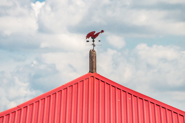 Shows the direction of the wind. Weathervane of a compass red cock on a red roof against the sky.