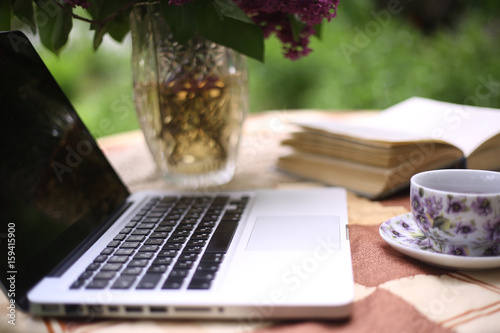 Laptop With Open Book And Tea Cup And Lilac Bouquet In Vase On