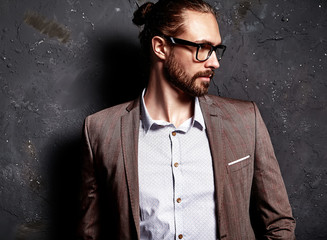 portrait of handsome fashion stylish hipster businessman model dressed in elegant brown suit in glasses posing near dark wall in studio