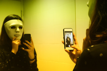 A girl with mystery white mask take her photo selfie in front of mirror by her mobile phone, dreamy color