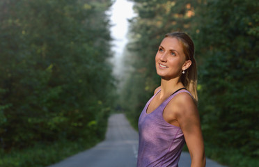 Portrait of sporty woman smiling and posing in a path